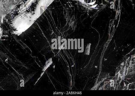 Strato sottile di ghiaccio rotto contro il nero. Texture di sfondo astratto con riflessioni. Foto Stock