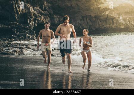 Gli adolescenti in esecuzione in acqua dell'oceano al tramonto. Gruppo di teen godendo di rottura di scuola jumping happy nel popolo del mare godere di una vacanza di divertimento Foto Stock