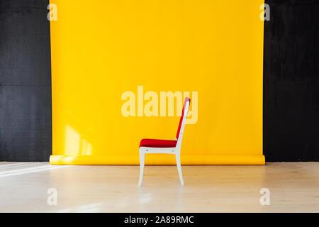 Una sedia rossa all'interno della camera con uno sfondo giallo Foto Stock