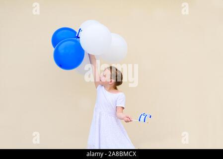 Capretto felice, grazioso piccolo ragazza caucasica ,l'età 8-9 con blu e bianco palloncini ans bandiera di Israele.vacanza patriottica Giorno Di Indipendenza Israele Yom ha atzmaut' concetto.Copia spazio per il testo. Foto Stock