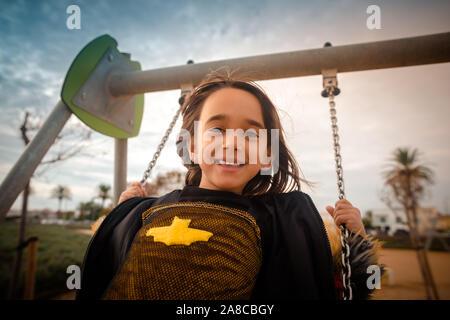 Inquadratura ravvicinata di una giovane ragazza europea felici giocando su un altalena in un parco all'aperto che indossa un costume di bat.