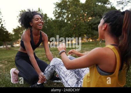 Allegro giovane femmina diversi amici ridere facendo ab sgranocchia su erba verde nel parco - amici ridere insieme mentre si fa esercizio all'aperto