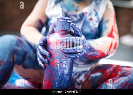 Un adorabile piccolo bambino, ragazza è divertente giocare con la colorazione di pitture, getting confuso e divertirsi un sacco, girato in un ambiente domestico Foto Stock