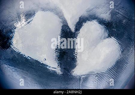 Due simboli di cuore incorporato in un blocco di ghiaccio Foto Stock