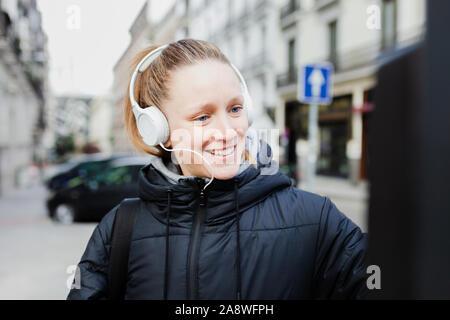 Giovane donna bionda di pagare il parcometro nella città con faccia sorpresa che indossa una giacca di un cuffie Foto Stock