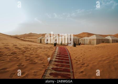 Splendido desert camp e tappeto sulla sabbia formando un corridoio con tende in background.