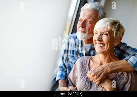 Felice coppia senior in amore abbracciando e legame con emozioni vere a casa Foto Stock