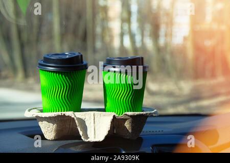 Verde di due bicchieri di carta con tè o caffè per un paio in auto sulla soleggiata sfondo sfocato. Takeaway, social media. La colazione del mattino in auto.