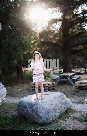 Ragazza sorridente in piedi sulla roccia Foto Stock