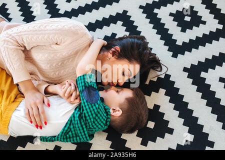 Giovane madre e il suo piccolo figlio abbraccia , guardando fra loro e giacenti sul piano Foto Stock