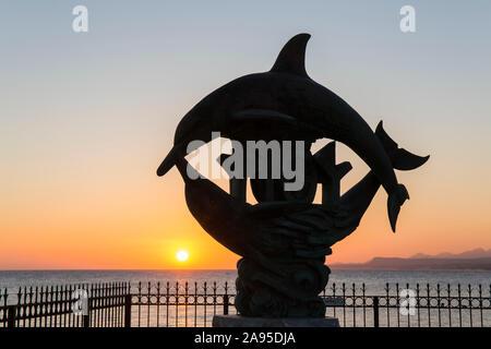 Rethymno, Creta, Grecia. Sagoma dell'iconica statua dei delfini all'alba.