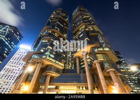 Basso angolo vista dei grattacieli moderni nel quartiere centrale degli affari di Hong Kong Island di notte nella RAS di Hong Kong, Cina