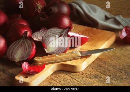 Le cipolle rosse su legno di spacco scheda di taglio su legno scuro texture rustico sfondo. Vista superiore, lo spazio per il testo