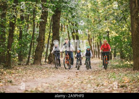 I genitori e i bambini ciclismo su pista forestale. Famiglia giovane in bicicletta nel parco d'autunno. Famiglia mountain bike sulla foresta. Tema famiglia active sport outdoor Foto Stock