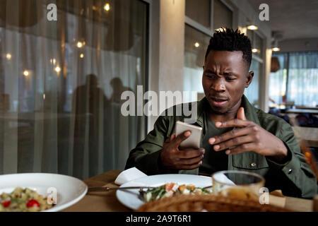 Giovani delusi sorpreso african american uomo online di messaggistica, controllo reti sociali in cafe. spazio copia