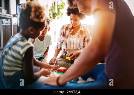 Felice famiglia nero giocando insieme a casa Foto Stock