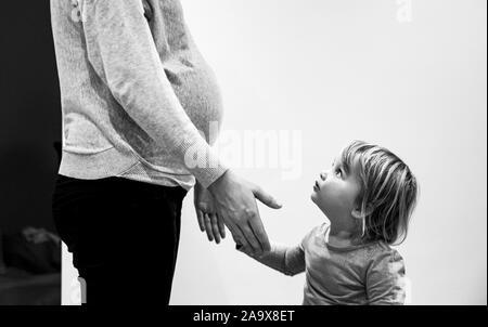 Donna incinta con la figlia di due anni e baby bump fotografia scattata da Simon Dack Foto Stock