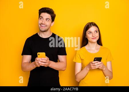 Foto di due positivi divertente carino bel marito e moglie insieme gente trendy ed elegante interrogandosi su che cosa tipo azienda navigazione telefoni vestita di nero t