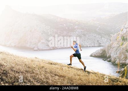 L'uomo atleta che corre in salita su sfondo Baia Mare in sunset Foto Stock