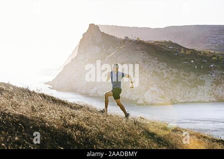 Uomo sportivo in esecuzione sentiero di montagna in salita al tramonto e la luce del sole Foto Stock