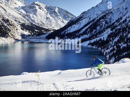 Ciclista giostre a neve a riva del lago di montagna ad Almaty in Kazakistan Foto Stock