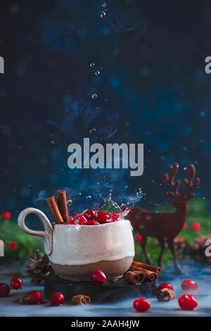 Mirtillo palustre bevanda invernale con gocce d'acqua, cannella, di vapore e di una decorazione in legno di cervo.