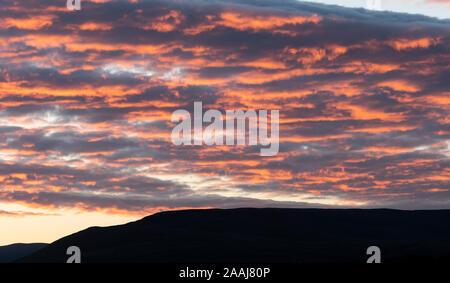 Nuvole cattura l'ultimo bit del sole serale e bagliore arancione, al di sopra del Yorkshire Dales in Wensleydale, UK. Foto Stock