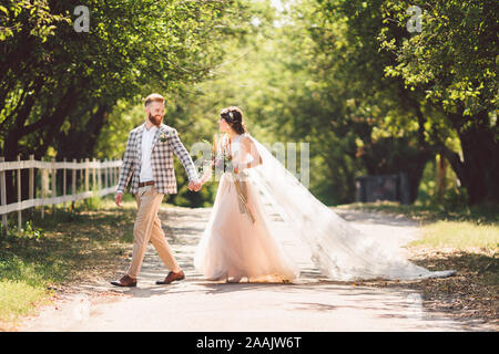 Bel matrimonio coppia legno foresta. Sposa e lo sposo, follow me coppia sposata, donna in bianco abito da sposa e il velo. Rustico all'aperto storia d'amore Foto Stock