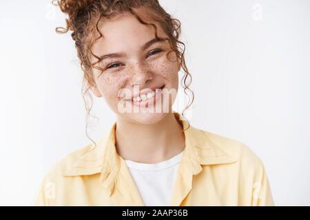 Splendida caucasica ragazza di zenzero lentiggini ricci disordinati bun testa tiltante friendly piacevolmente sorridente esprimere ottimismo, sentire felice rilassata, in piedi Foto Stock