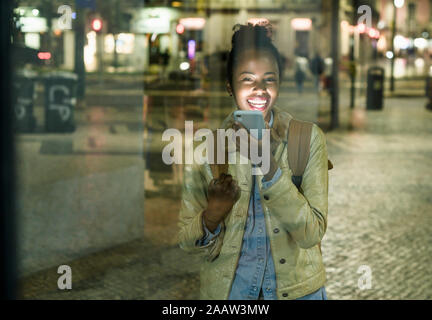 Ritratto di ridere giovane donna al telefono nella città di notte, Lisbona, Portogallo Foto Stock