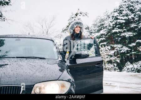 Sorridente giovane donna in piedi accanto a auto parcheggiata in inverno foresta guardando a distanza Foto Stock