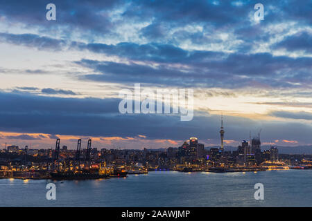 Edifici moderni per mare contro il cielo nuvoloso al tramonto a Auckland, Nuova Zelanda