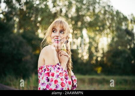 Ritratto di giovane donna che indossa abiti estivi con disegno floreale in natura Foto Stock