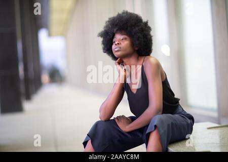 Piuttosto giovane americano africano donna su strade cittadine, seduta sul banco di lavoro Foto Stock