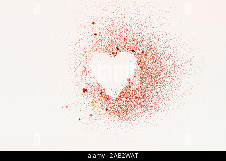 Forma di cuore fatta di red glitter e stelle su uno sfondo bianco. Il giorno di San Valentino, la minima nozione d'amore.