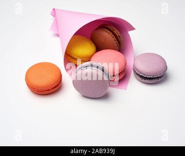 Macarons cotti al forno in un rosa sacchetto di carta su uno sfondo bianco, vicino.