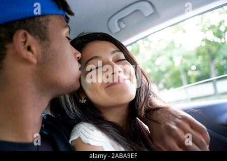 Coppia giovane seduti insieme nel sedile posteriore della vettura.