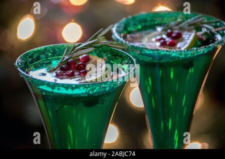 Champagne flauti close up, tenere la spumeggiante bevanda alcolica, guarnito con una fetta di lime, i semi di melograno e un rametto di rosmarino Foto Stock
