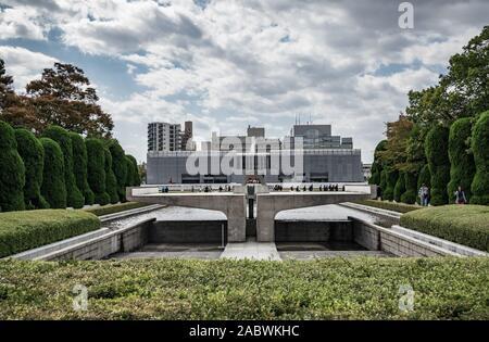 I turisti passeggiano in Hiroshima Parco del Memoriale della Pace di Hiroshima, Giappone con l'Hiroshima Peace Memorial Museum in background. Foto Stock