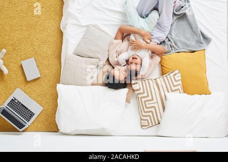 Angolo di alta vista di felice giovane madre giacente e abbracciando il suo bambino nel letto in camera da letto a casa Foto Stock