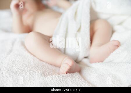 Neonato neonato sdraiato sul letto con coperta Foto Stock