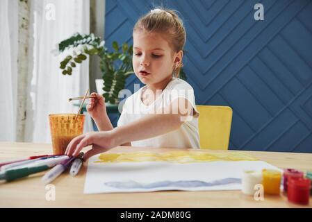 Tenendo marcatore. Bambina è il disegno utilizzando gouache e spazzola. L'apprendimento in classe d'arte Foto Stock
