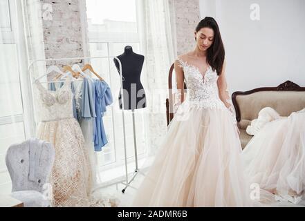 In piedi di fronte allo specchio. Il processo di montaggio del vestito in studio di lavorati a mano i vestiti