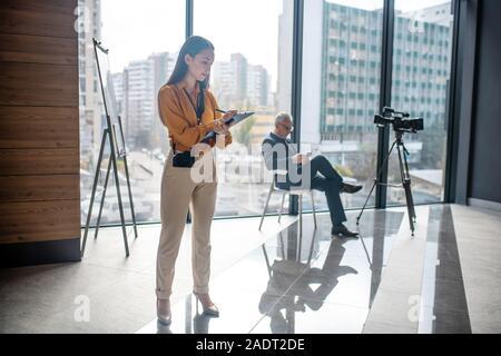 Giovane ed elegante reporter femmina in piedi in studio