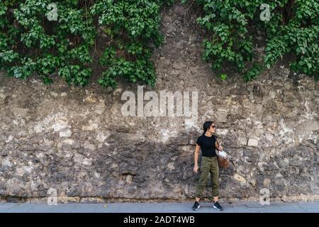 Attivo giovane donna con il suo sacchetto appeso accanto a un muro di pietra cercando