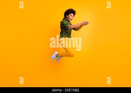Foto completa del corpo di crazy pelle scura curly lady jumping elevata rendendo il nuoto si muove eccitato per avviare la concorrenza usura verdi punteggiate shirt pantaloni