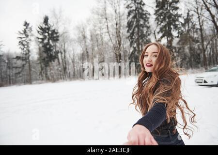 Bel rosso labbra. La ragazza con i capelli lunghi va vicino alla foresta per l'automobile in inverno Foto Stock