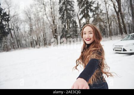 So dove andremo a finire. La ragazza con i capelli lunghi va vicino alla foresta per l'automobile in inverno Foto Stock