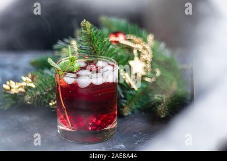 Holiday melograno drink con ghiaccio. Una finestra nevoso, sullo sfondo dei rami di abete rosso. Nuovo anno. Natale. Primo piano. Foto Stock