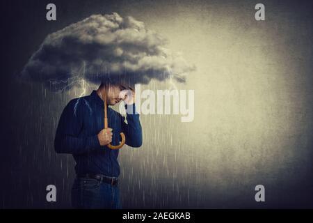 Uomo pessimista, in piedi sotto la pioggia, soffrono di ansia con ombrello tempesta nuvola sulla testa. Concetto di perdita della memoria e demenza disea